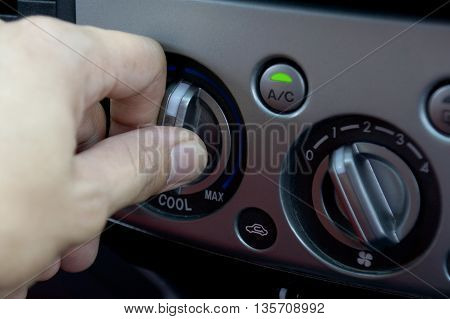 Left hand adjusting a temperature control knob of the car's air conditioning system.