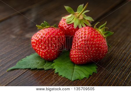 Fresh tasty strawberries with on old wooden background