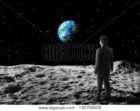businessman walks on moon surface - business concept