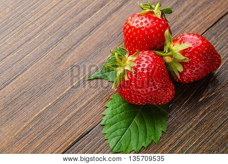 Three fresh strawberries with leaves on old wooden background