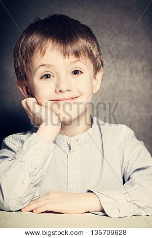 Smiling Child Boy Sits at a School Desk