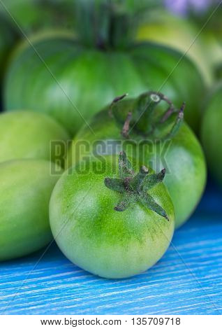 Green tomatoes on blue wooden background. Fresh vegetables.