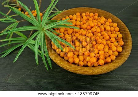 Sea-buckthorn berries in bowl on a wooden background