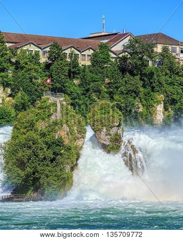 The Rhine Falls in summertime. The Rhine Falls is the largest plain waterfall in Europe located on the Rhine river in Switzerland.