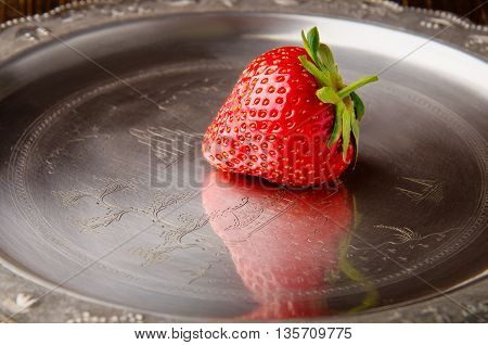 Single tasty red strawberry on a vintage plate closeup
