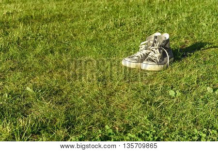 youth sneakers lie on the green grass
