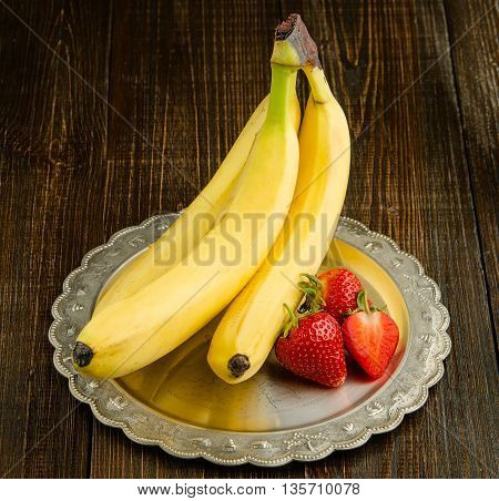 Bananas with strawberries on a vintage plate