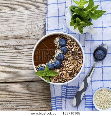 Healthy breakfast or snack. A bowl of thick chocolate banana smoothies garnished with blueberries, granola cereal, seed, sprig of fragrant oregano
