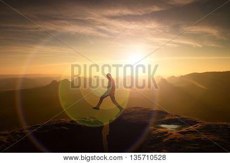 Jumping hiker in black celebrate triumph between two rocky peaks. Wonderful daybreak. Strong lens defect