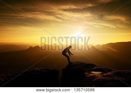 Man In Black Jumping Between Peaks. Dreamy Daybreak