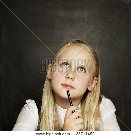 Little beutiful girl on dark blackboard background