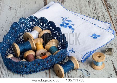 Knitted basket with old wooden spool of thread, a napkin with embroidery and thimble on a light wooden background.