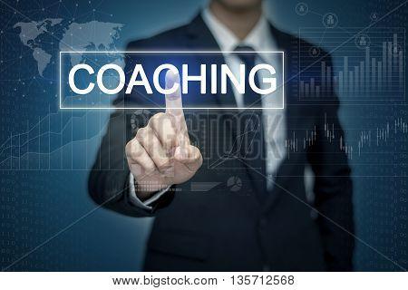 Businessman hand touching COACHING button on virtual screen