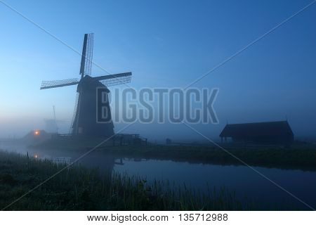 Traditional Dutch windmill during sunrise in The Netherlands