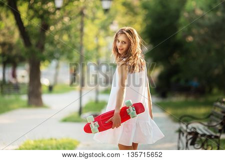 Portrait Of Lovely Urban Girl In White Dress With A Pink Skateboard