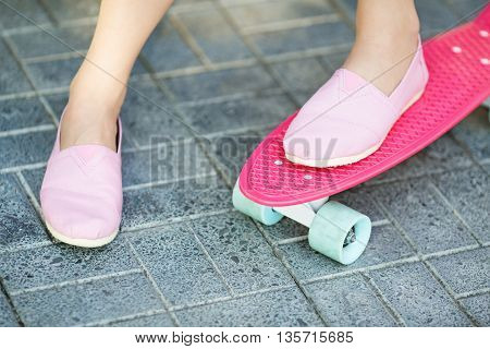 Girl Standing On A Pink Skateboard Outdoors