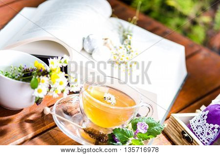 Cup of tea on a wooden backgound. Flowers and grass. Natural background. Agricultural.Garden