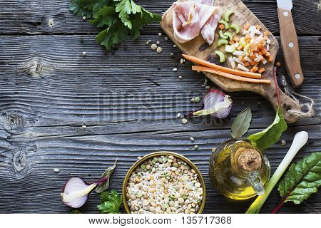 Ingredients for home-flavored soup with lentils, bacon, carrots, celery, onion, pepper, herbs, spices, olive oil on a wooden cutting board with a background from the olive tree.