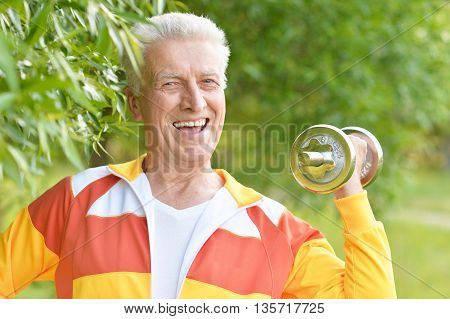 Elderly man exercising with dumbbell in  park