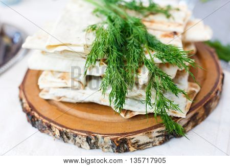 Stack of homemade whole wheat flour tortillas with fresh dill on wooden round desk. Pitas for sale with fennel at picnic outdoors, closeup.