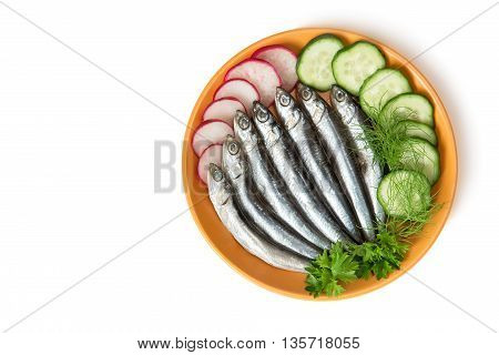 On the yellow plate small salted fish anchovies next to the cucumbers with parsley dill. Presented on a white background.