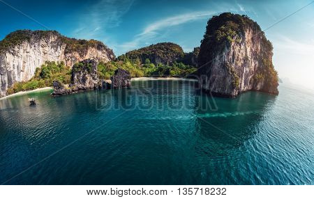 Island with a sandy beach and huge rocky cliff in the Andaman sea. The island of Koh Hong