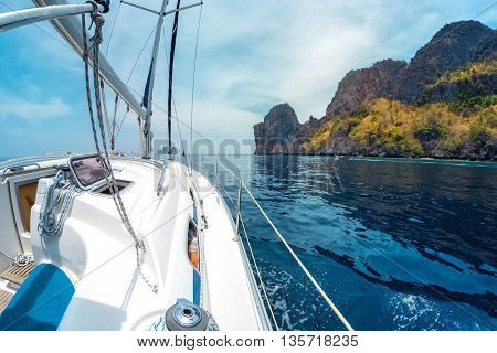 Sail boat in the sea passing by rocky island