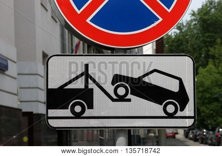 road sign of tow truck evacuator with reflective layer on the streets of Moscow