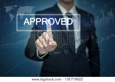Businessman hand touching APPROVED button on virtual screen