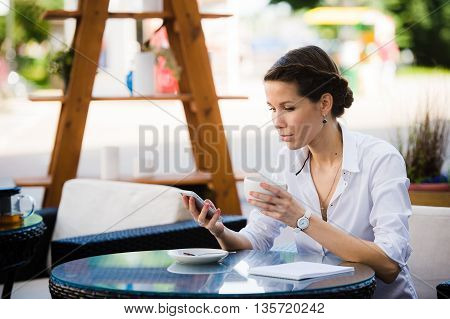 Portrait of young businesswoman drinking coffee and using mobile phone while sitting at the sidewalk cafe.