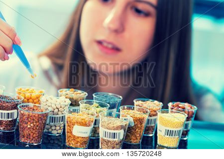 girl in the laboratory of food quality tests legumes grain. Toned photo