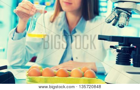 girl in the laboratory testing of food quality egg. Check the content of protein, fat, cholesterol and pathogens. Toned photo