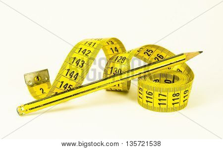 still life with a yellow tape measure and a pencil over white