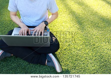 man sitting use laptop on artificial turf