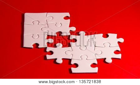 still life with a white jigsaw/puzzle incomplete over a red background symbol of problem solving