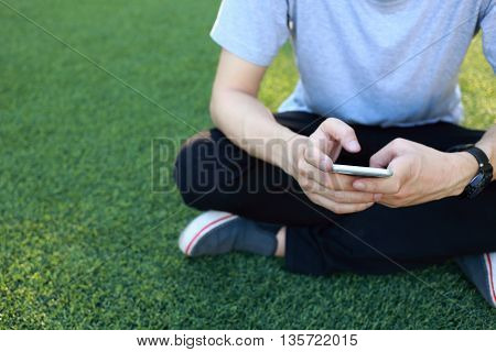 man sitting use smartphone on artificial turf