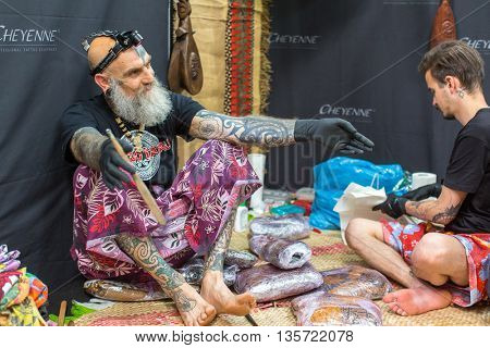KRAKOW, POLAND - JUNE 12, 2016: Unidentified festival participant make a tattoos at the 11-th International Tattoo Convention in the Congress-EXPO Center of Krakow.