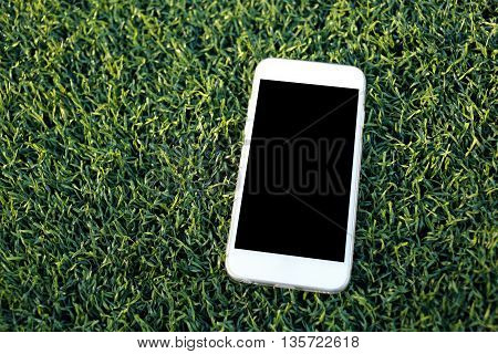 smartphone with blank screen on artificial turf