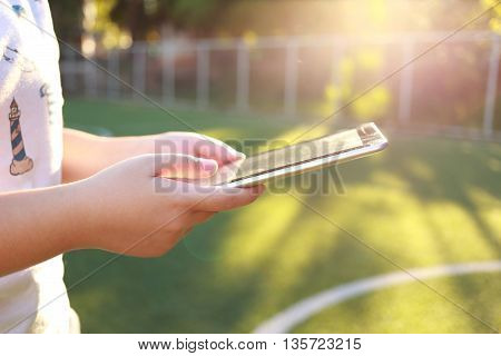 Woman holding and use tablet on green grass