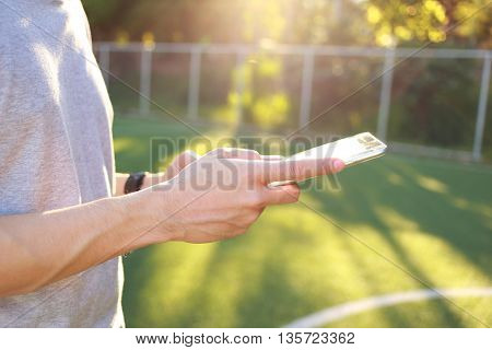 Hand holding tablet on a green grass