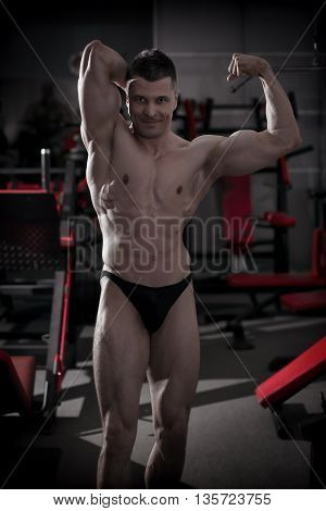 Handsome bodybuilder posing in gym. Perfect muscular male body. Toning image