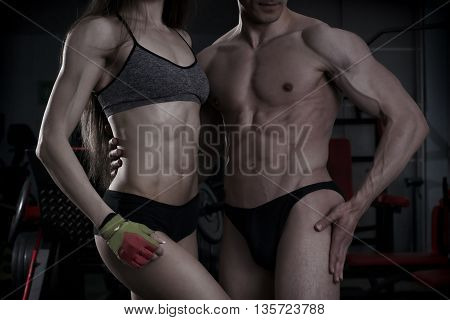 Young sexy athletic man and woman after fitness exercise. Perfect muscular body. Toning image