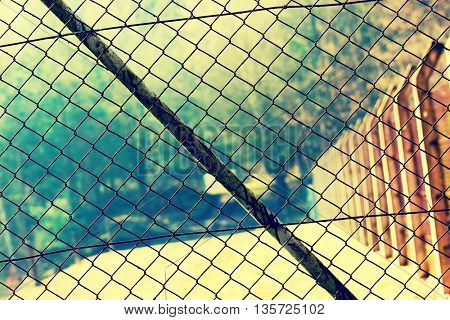 Mesh netting Rabitz on the fence. Toned photo