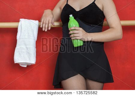 Midsection Of Ballerina Holding Bottle Against Wall