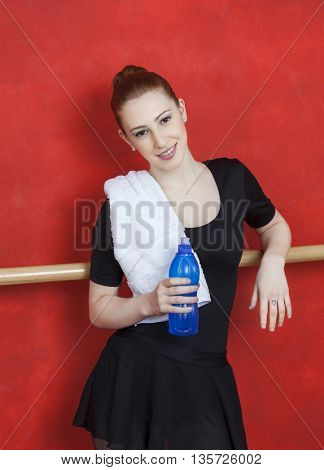 Ballerina Holding Water Bottle Against Red Wall