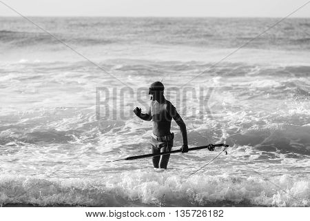 Diver with spear gun line buoy beach ocean swimming entry black and white..