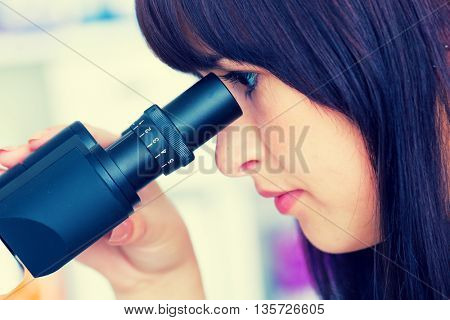 technician in the laboratory using a microscope. Toned photo