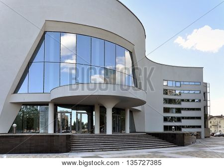 Grodno, Belarus - June 22, 2016: Facade of modern Philharmonic. Concert hall with curved walls and mirrored windows. Restored building. Grodno, Belarus.