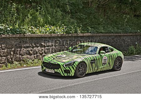 PASSO DELLA FUTA (FI) ITALY - MAY 21: driver and co-driver on a supercar Mercedes-Benz AMG GT-S (2016) green tiger painted in historical italian race Mille Miglia on May 21, 2016 in Passo della Futa (FI) Italy