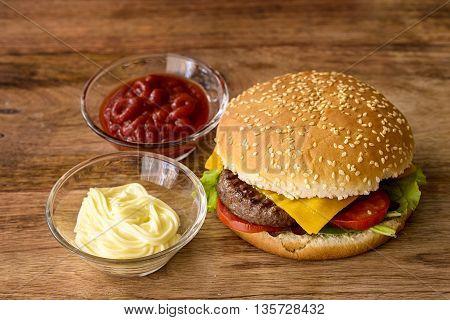 cheeseburger, cheddar, burger, salad and tomato with mayonnaise and ketchup on wood